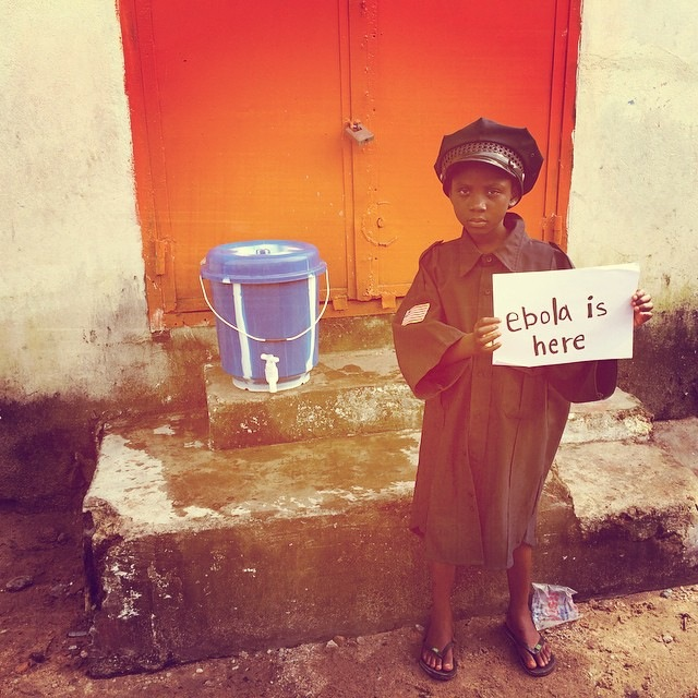 "Mamawa, a More Than Me student, holding up an ""Ebola is here"" sign. She wants to be a police officer day, so she was trying on the uniform for size. (Instagram.com/katiemeyler, More Than Me)"